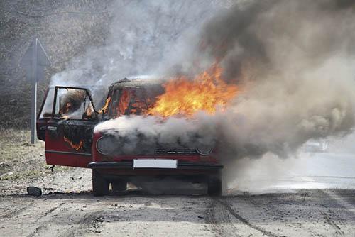 Burning car on desert rural road